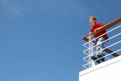 El muchacho se coloca en cercar con barandilla en la cubierta de la nave Imagenes de archivo