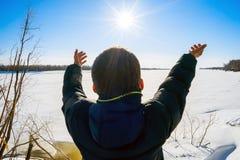 El muchacho se coloca en el río congelado orilla y tirado a mano al sol Fotografía de archivo