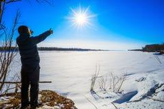El muchacho se coloca en el río congelado orilla y tirado a mano al sol Foto de archivo
