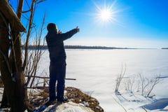 El muchacho se coloca en el río congelado orilla y tirado a mano al sol Imagen de archivo libre de regalías