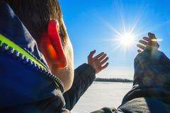 El muchacho se coloca en el río congelado orilla y tirado a mano al sol Imagenes de archivo
