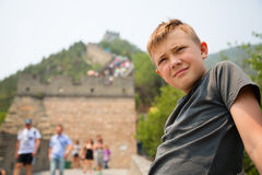 El muchacho se coloca en la Gran Muralla de China Imagenes de archivo