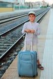 El muchacho se coloca en la plataforma del ferrocarril con el bolso del recorrido Imágenes de archivo libres de regalías