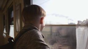 El muchacho se coloca en la ventana del tren y considera hacia fuera la ventana los paisajes corrientes Recorrido en tren Turismo almacen de video