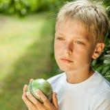 El muchacho se coloca en la yarda que sostiene la bola y comtempla Fotos de archivo