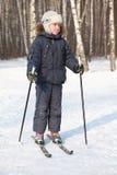 El muchacho se coloca en los esquís a campo través, invierno Imágenes de archivo libres de regalías