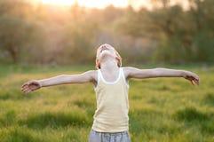 El muchacho se coloca en un prado Fotos de archivo libres de regalías