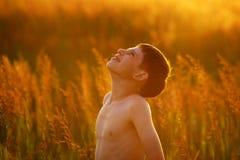 El muchacho se coloca entre la alta hierba del campo Imagen de archivo libre de regalías