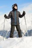 El muchacho se coloca que se inclina en postes de esquí y de mirada hacia arriba Imagenes de archivo