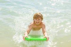 El muchacho se divierte con la tabla hawaiana Imagen de archivo
