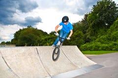 El muchacho se divierte con su BMX en el skatepark Imagenes de archivo