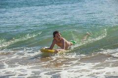 El muchacho se divierte el practicar surf en las ondas Imágenes de archivo libres de regalías