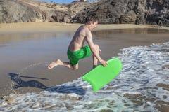 El muchacho se divierte el practicar surf en las ondas Foto de archivo