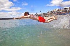 El muchacho se divierte en el mar claro Fotografía de archivo