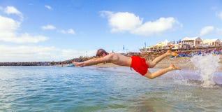 El muchacho se divierte en el mar claro Foto de archivo