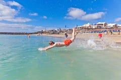El muchacho se divierte en el mar claro Imagen de archivo libre de regalías