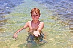 El muchacho se divierte en el océano claro Foto de archivo
