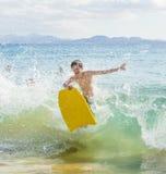 El muchacho se divierte en el océano con su tablero de la boogie Imágenes de archivo libres de regalías