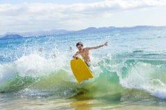 El muchacho se divierte en el océano con su tablero de la boogie Imagenes de archivo
