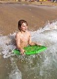 El muchacho se divierte en la playa Foto de archivo