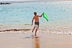 El muchacho se divierte en la playa Fotografía de archivo