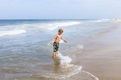 El muchacho se divierte en la playa tempestuosa Fotos de archivo
