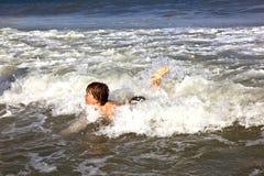 El muchacho se divierte en los trituradores del océano Foto de archivo libre de regalías