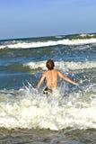 El muchacho se divierte en los trituradores del océano Imagen de archivo libre de regalías