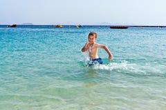 El muchacho se divierte que corre en el agua Fotografía de archivo libre de regalías