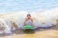 El muchacho se divierte que practica surf en las ondas Imagenes de archivo