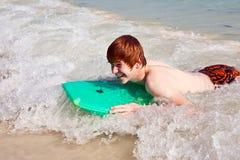 El muchacho se divierte que practica surf en las ondas Fotografía de archivo