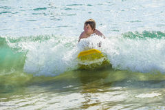 El muchacho se divierte que practica surf en las ondas Foto de archivo