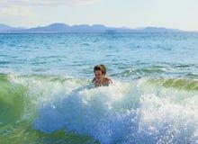 El muchacho se divierte que practica surf en las ondas Fotografía de archivo libre de regalías