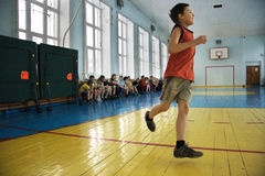 El muchacho se ejecuta en escuela de la educación física Imagen de archivo