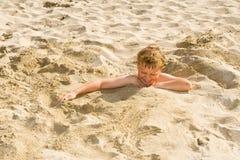 El muchacho se está cavando en la playa arenosa Fotografía de archivo