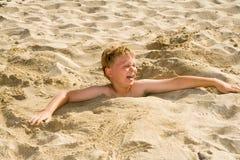 El muchacho se está cavando en la playa arenosa Fotos de archivo