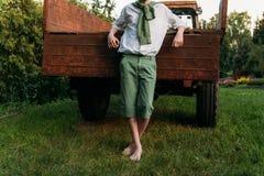 El muchacho se está inclinando en el viejo primo del camión, descalzo en la hierba en el verano Manos en bolsillos Foto de archivo libre de regalías