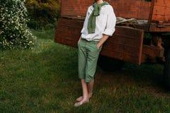 El muchacho se está inclinando en el viejo primo del camión, descalzo en la hierba en el verano Manos en bolsillos Foto de archivo