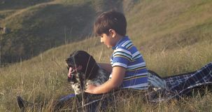 El muchacho se está sentando en la alfombra y el juego con un perro almacen de video