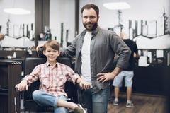El muchacho se está sentando en la peluquería de caballeros del ` s del peluquero Foto de archivo libre de regalías