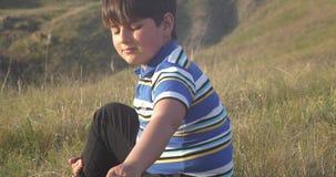 El muchacho se está sentando en la piedra y el juego con un perro almacen de metraje de vídeo