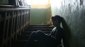 El muchacho se está sentando en los pasos de un pórtico abandonado El concepto de drogadicción del ` s de los niños, vagancia, fa almacen de metraje de vídeo
