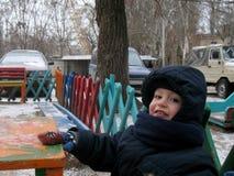 El muchacho se está sentando en el patio durante un paseo del invierno Imágenes de archivo libres de regalías