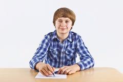 El muchacho se está sentando en su escritorio y está haciendo su preparación Foto de archivo libre de regalías
