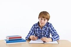 El muchacho se está sentando en su escritorio y está haciendo su preparación Imágenes de archivo libres de regalías