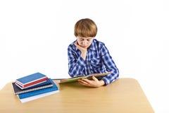 El muchacho se está sentando en su escritorio y está haciendo su preparación Imagenes de archivo