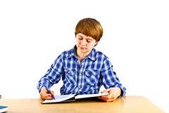 El muchacho se está sentando en su escritorio y está haciendo su preparación Fotografía de archivo
