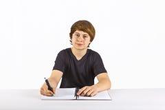 El muchacho se está sentando en su escritorio y está haciendo su preparación Fotografía de archivo libre de regalías