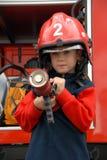 El muchacho se está sentando en un coche de bomberos Fotografía de archivo