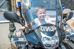 El muchacho se está sentando en una motocicleta de la policía el día de la policía marcado en Novi Sad imagenes de archivo